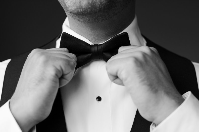 black and white groom tightens his bow on wedding day