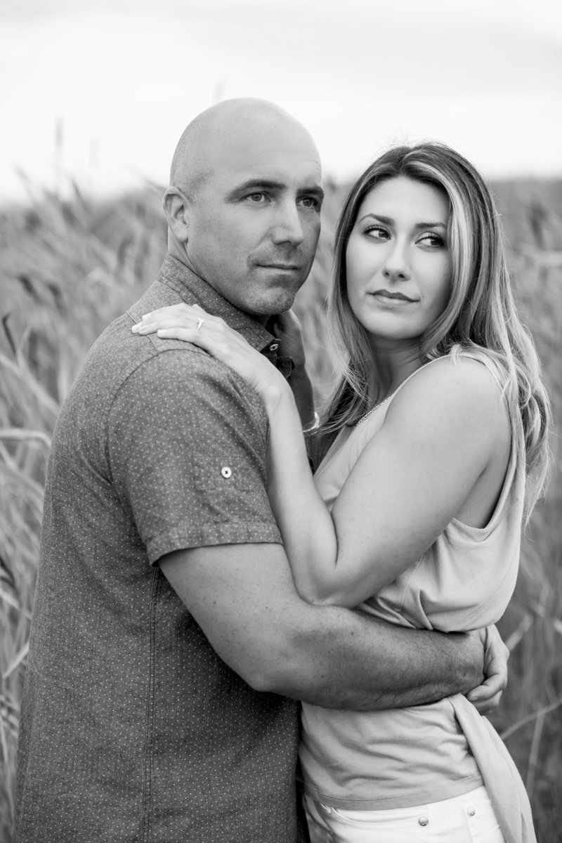 black and white of couple looking off camera in field