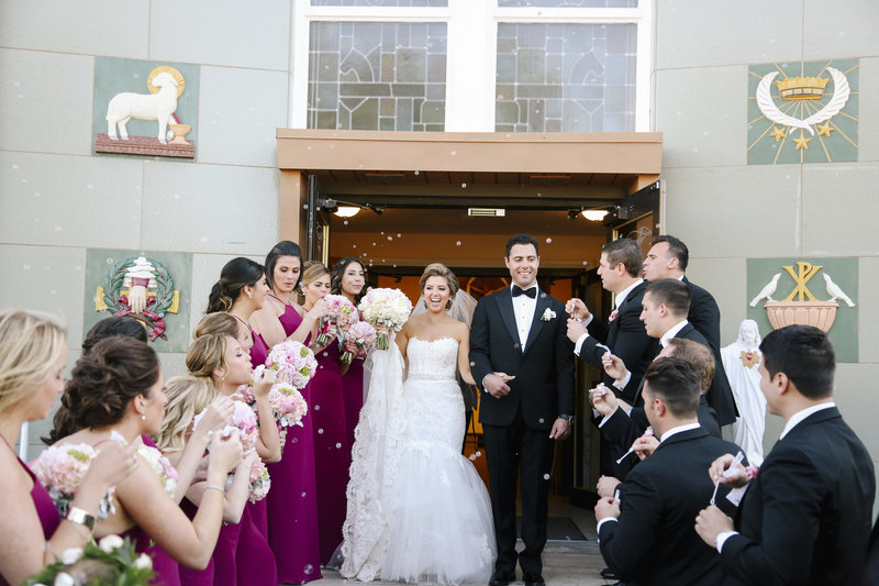 bride and groom exit church bridal party cheers bubbles