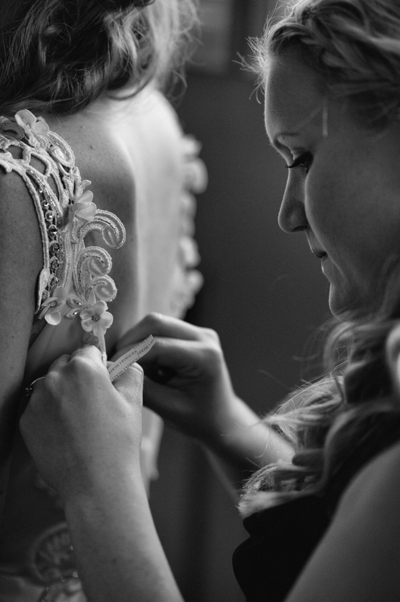 A detail wedding photography shot of the maid of honor helping the bride get ready at Eagle Crest Resort. Pete Erickson Photography.