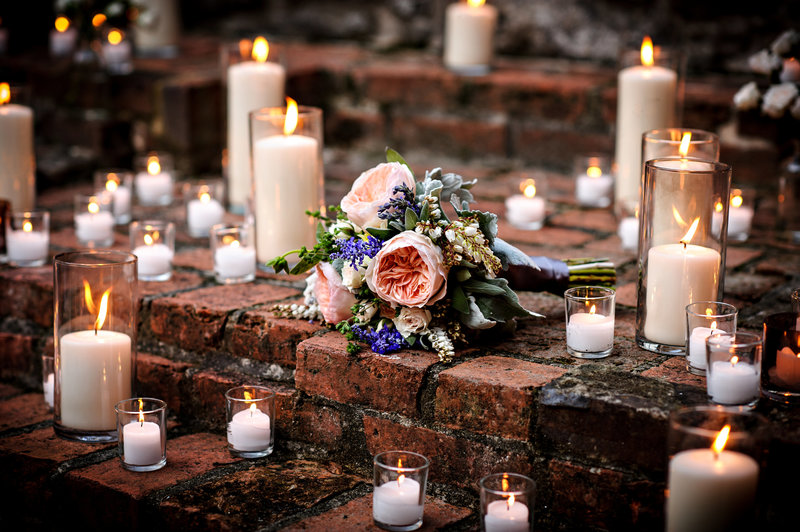 A bouquet of flowers surrounded by candles at a wedding in MD at the Patapsco Female Institute.