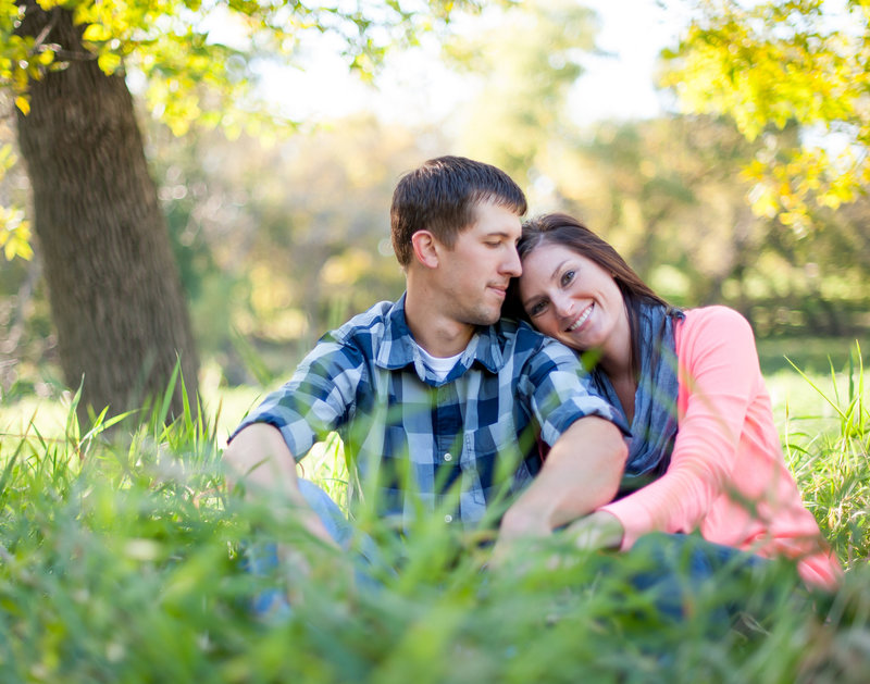 Sitting in the tall grasses an engagement session for Fargo couples photographed by Kris Kandel