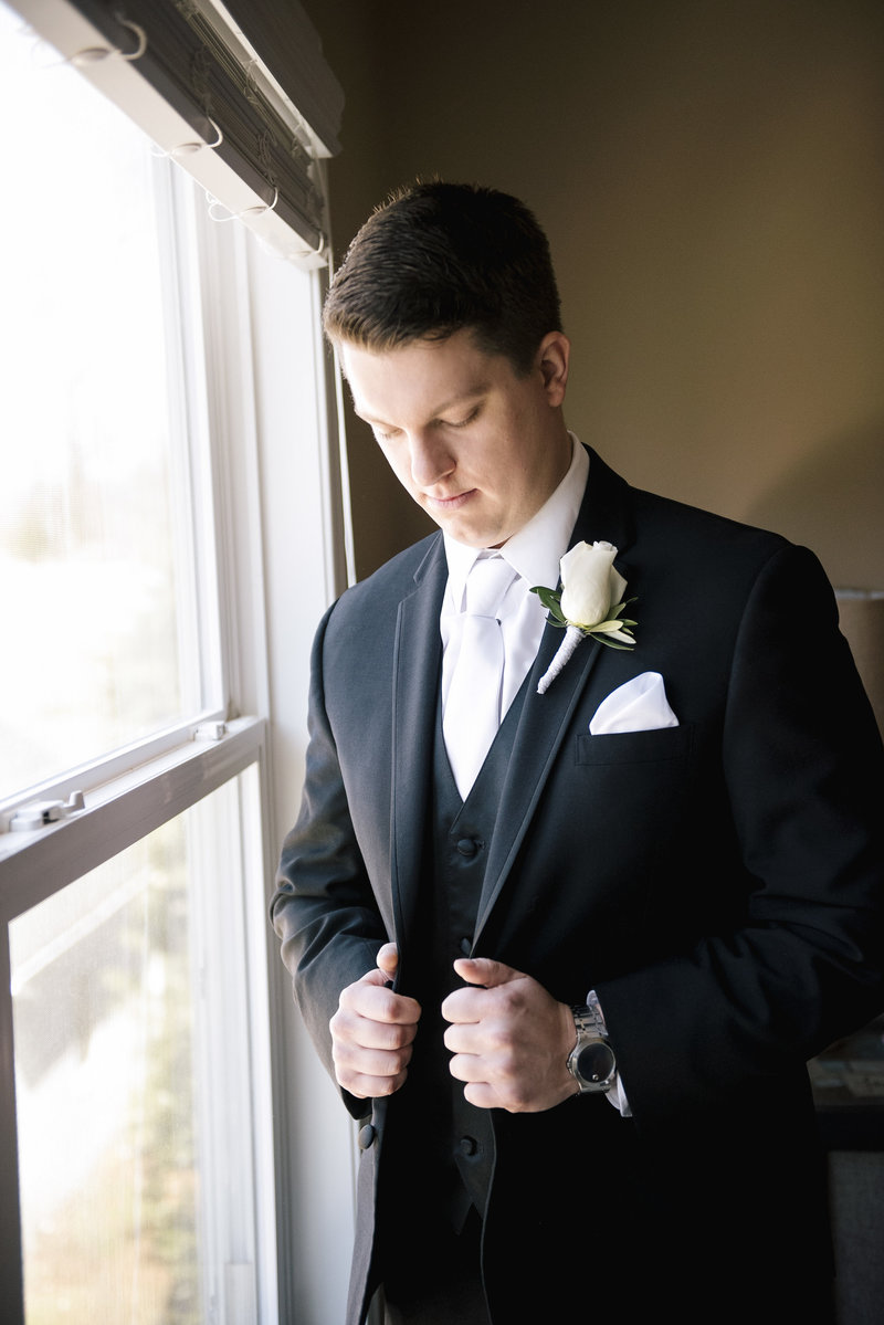 groom puts on coat in front of a window