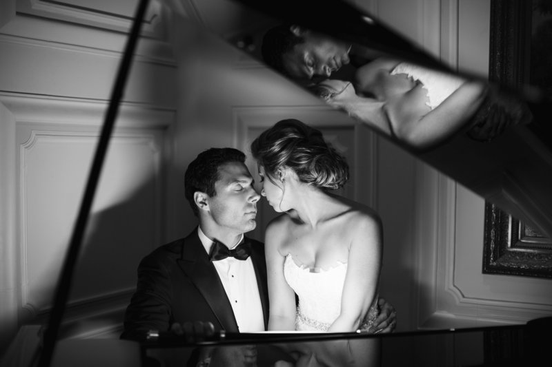 black and white groom and bride sit at piano with their reflection on top
