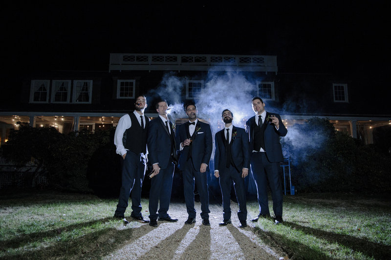 groomsmens stand in a row smoking cigars at night