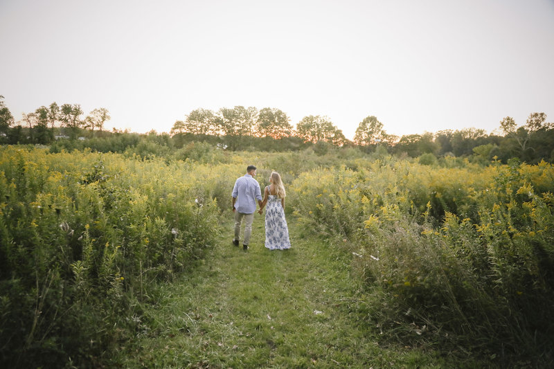 couple holding hands and walking away in a large green field