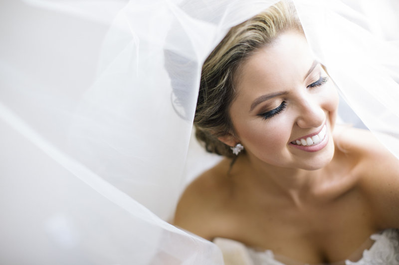 bride smiling under veil in amsale dress