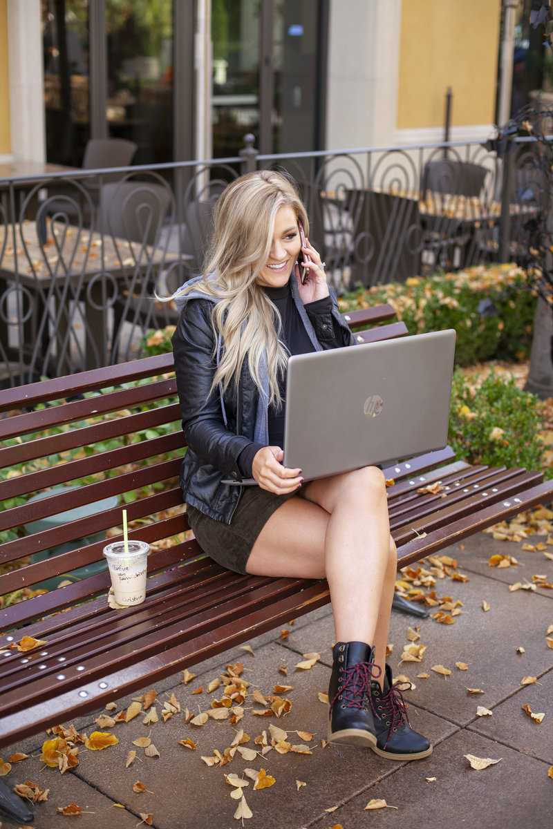 portrait of business owner on bench working on laptop