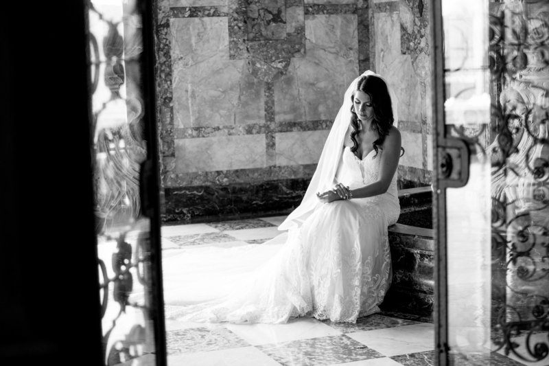 black and white candid portrait of bride sitting at fountain at monmouth university