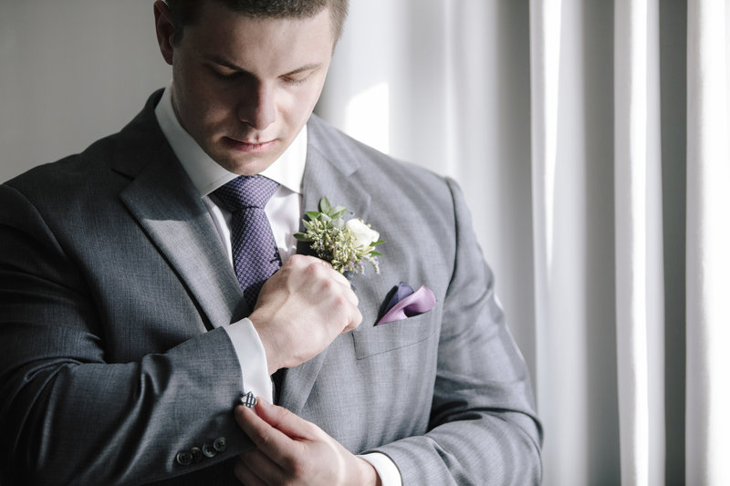 groom fixes his cuff links