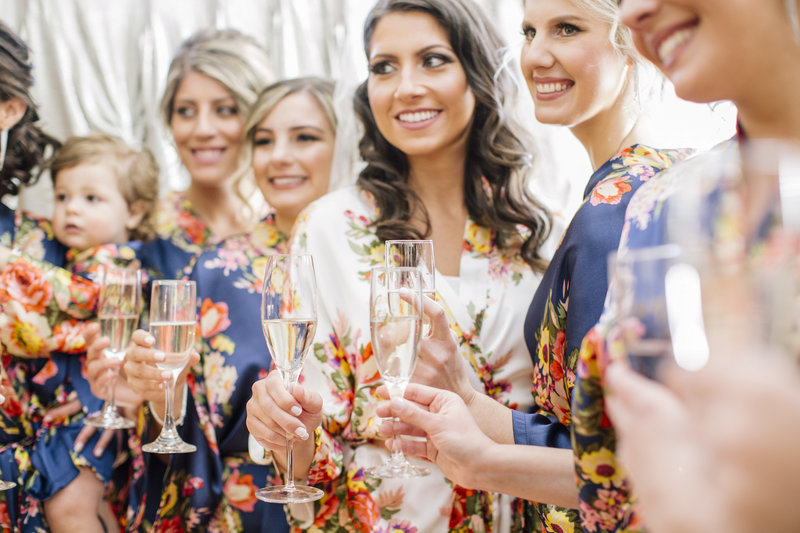 bride and bridesmaids in floral robes make a toast