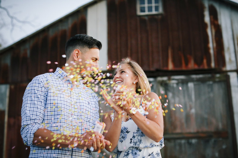 couple popping confetti poppers in front of large brown barn