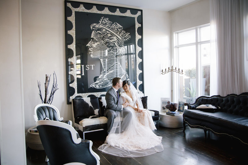 bride and groom sitting on cow skin couch in front of a large black painting