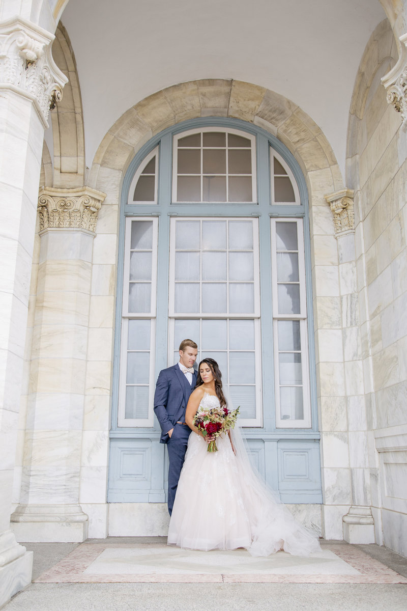 full length bride and groom in front of blue window