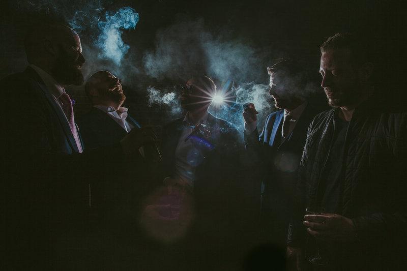 Een kick ass rookfoto van rokende bruidegom met zijn vrienden. Strobist. Door trouwfotograaf Nanda Zee van FOTOZEE