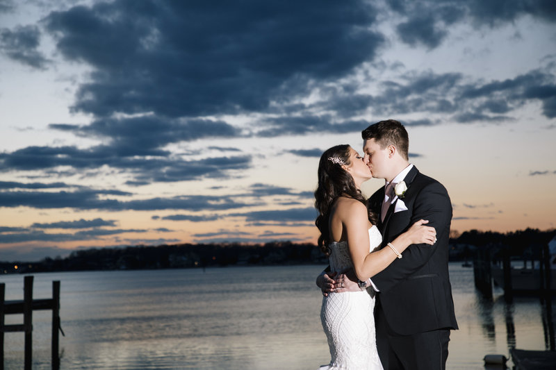 bride and groom kissing on a dock at sunset at clarks landing yacht club