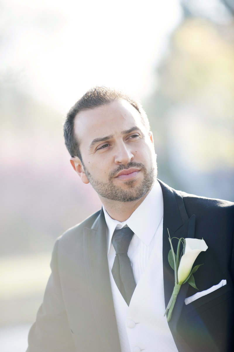 groom portrait in park with cherry blososms