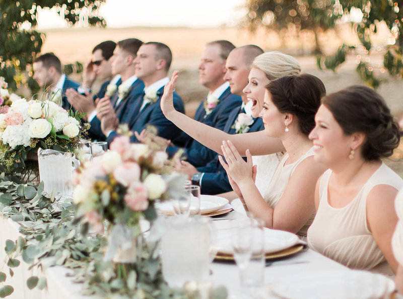 bridal party sitting at table during wedding reception
