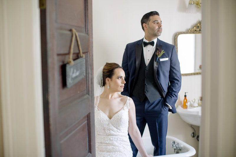 groom in old claw foot  bath tub bride sits on side