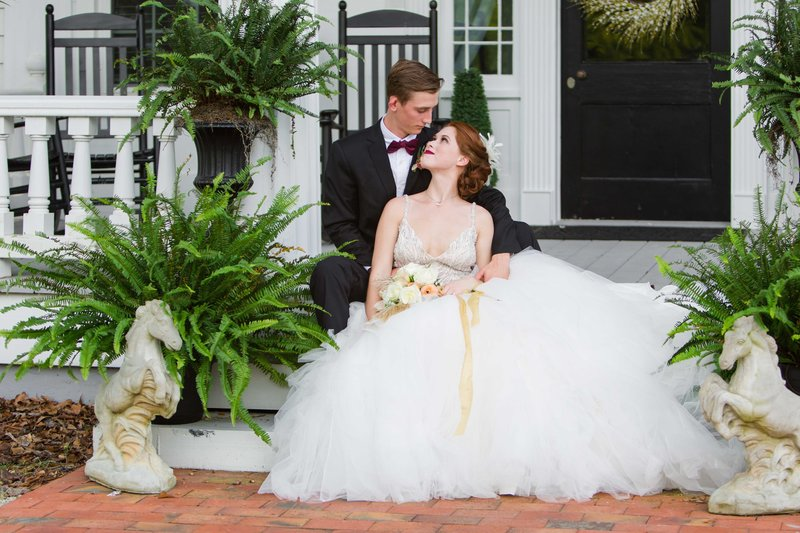 Wedding couple sits on Parterred porch steps
