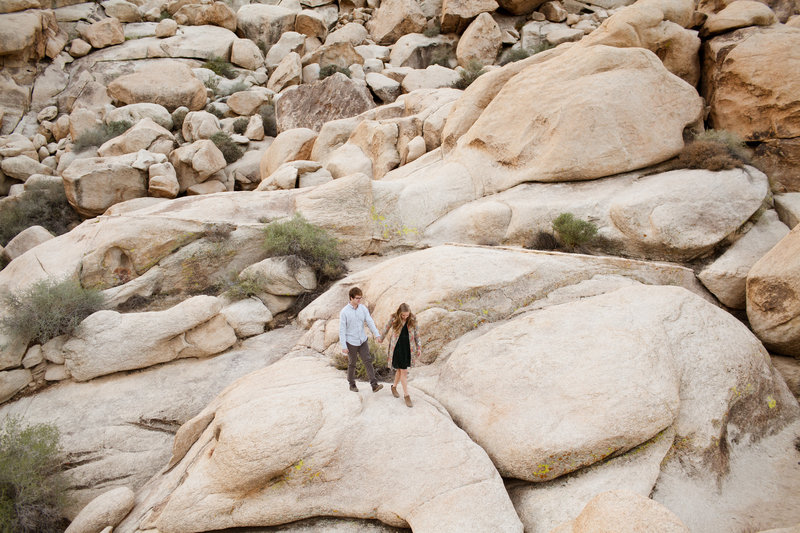 couple holding hands in joshua tree national park for their engagement photos