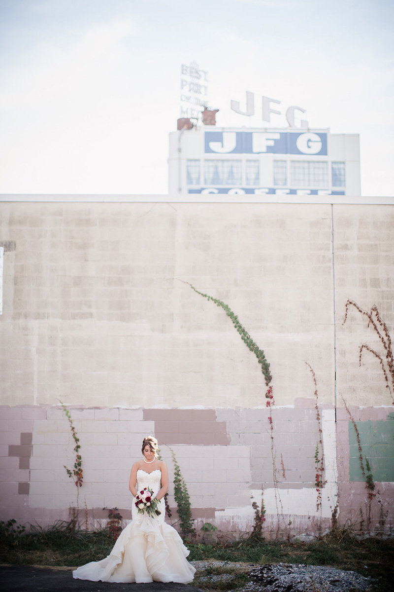 Bride in front of downtown building with JFK sign at Jackson Terminal Wedding Venue by Knoxville Wedding Photographer, Amanda May Photos.