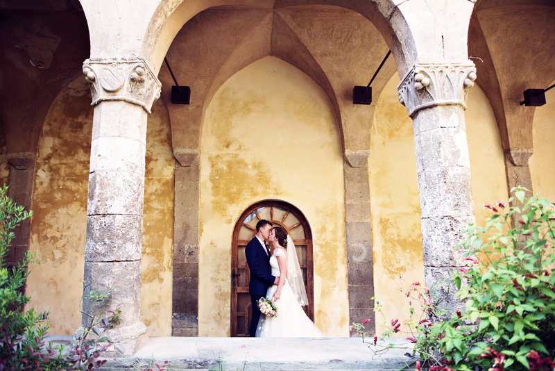 Bride and Groom under the arches of The San Francesco Cloisters Sorrento Italy