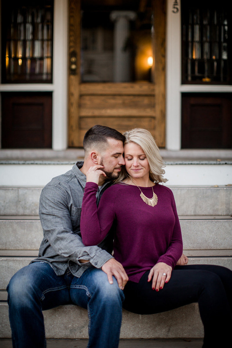 Sitting on the stairs with her hand back on his cheek in downtown Knoxville by Knoxville Wedding Photographer, Amanda May Photos.