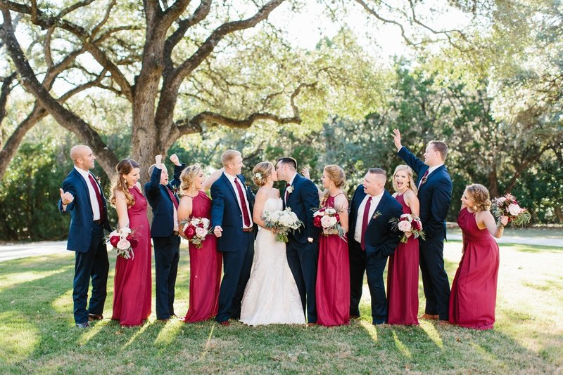 Wedding party wearing navy suits and bridesmaids in  burgundy dresses