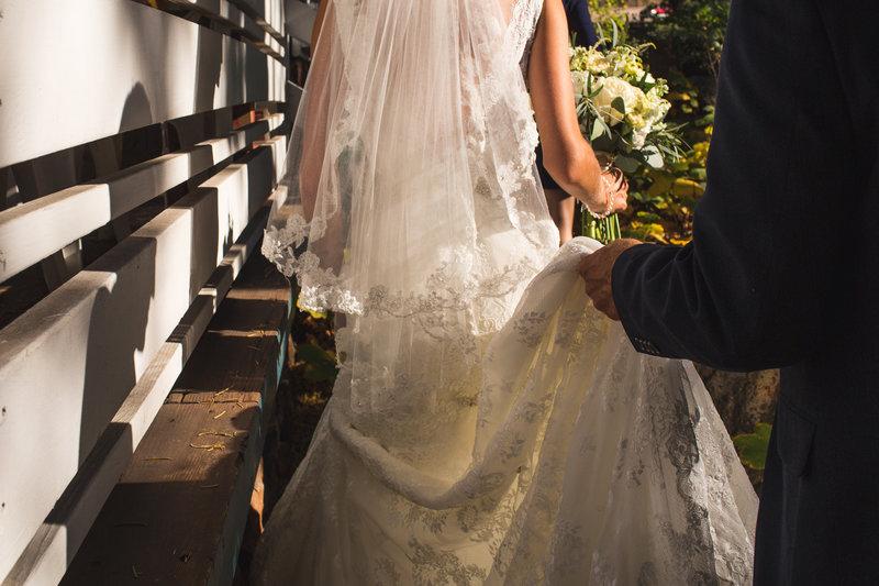 Lake Tahoe Wedding Photographer Destination Wedding groom holding brides lace train