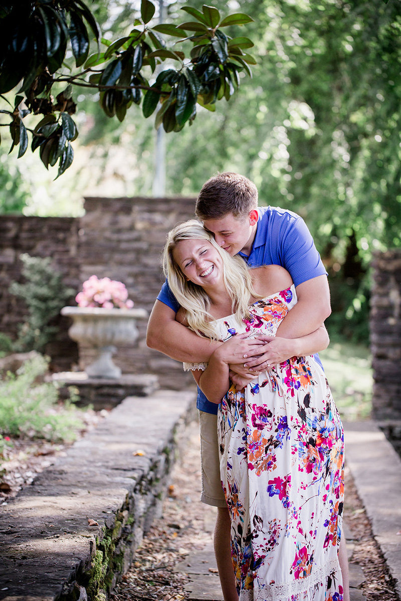 He hugs her from behind with a long floral dress on at Knoxville Botanical Gardens by Knoxville Wedding Photographer, Amanda May Photos.