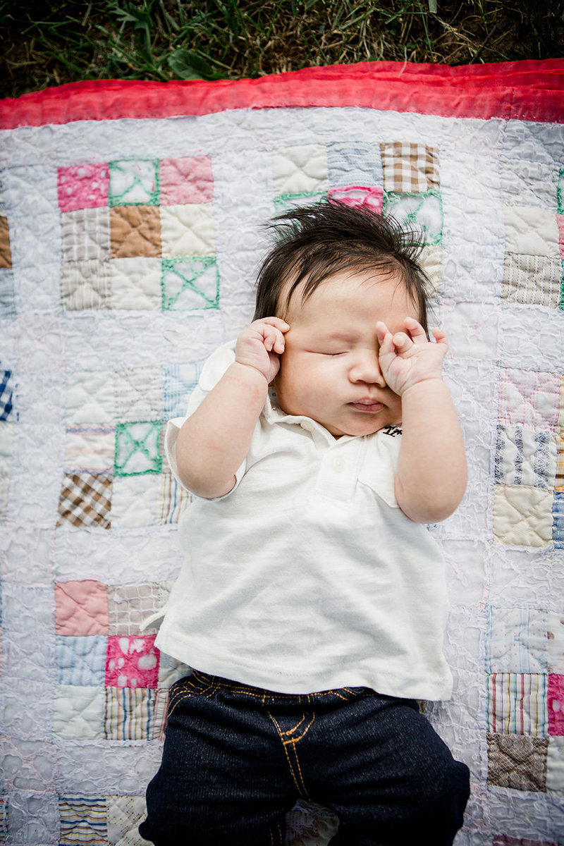 Little asian boy wiping his eyes laying on a hand sewn quilt by Knoxville Wedding Photographer, Amanda May Photos.