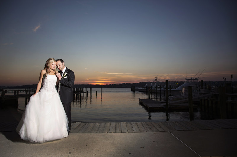 bride and groom on dock with sunset