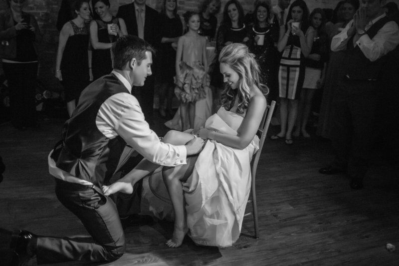 Groom removing garter from bride's leg