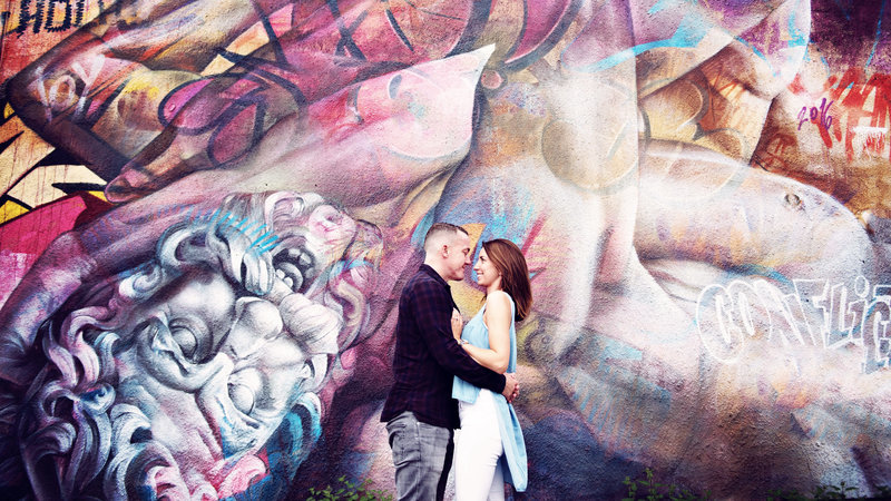 Bride and groom to be smile and cuddle in front of a cool graffiti wall in Manchester northern quter