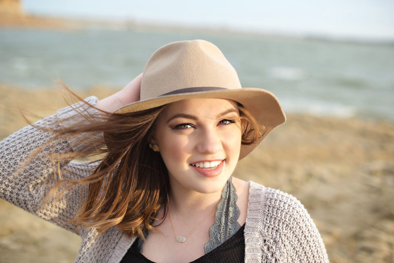High School Senior wearing a hat Photo at Rockledge Park in Grapevine Texas on a Windy Day