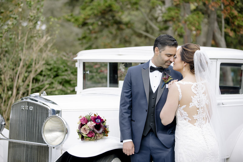 bride and groom in front of old rolls-royce car