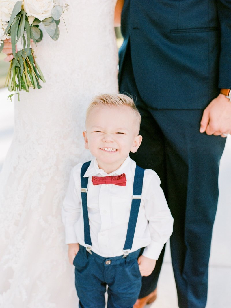ring bearer in suspenders and red bow tie