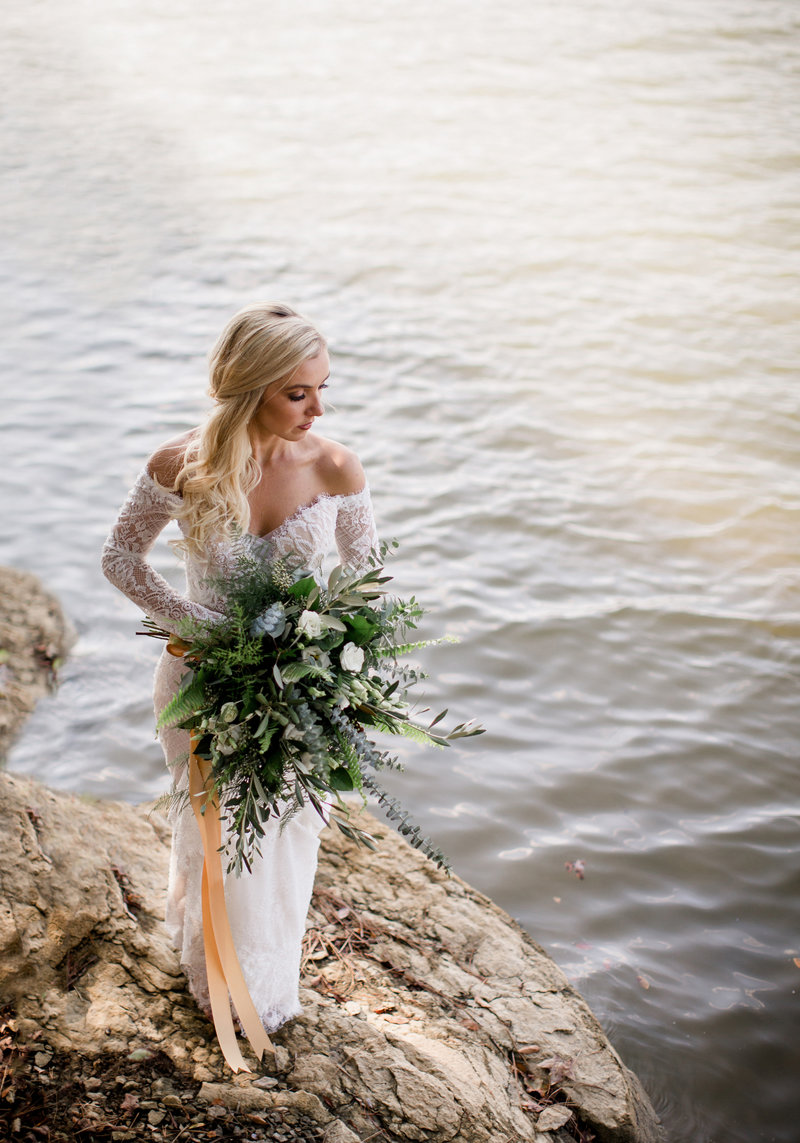 Bride standing on a rock in the water at Hunter Valley Pavilion at Knoxville Wedding Photographer, Amanda May Photos.
