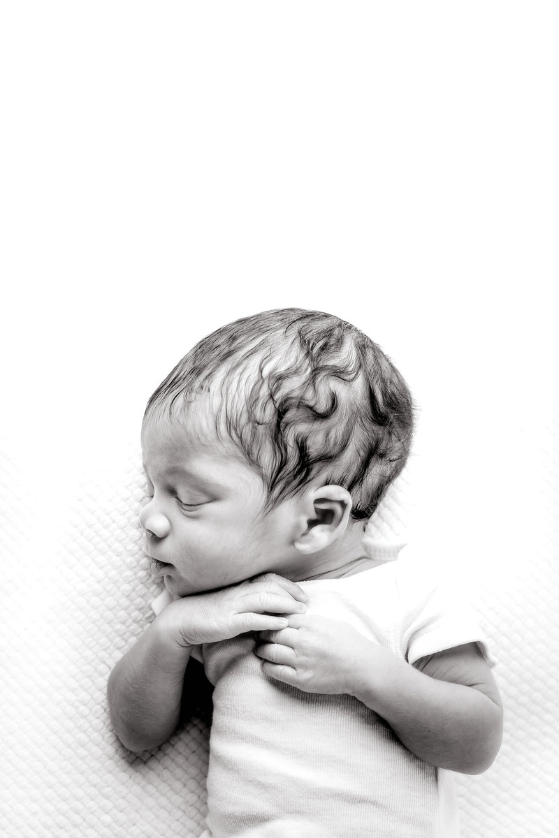 Black and white photo of baby boy laying on his back with his hands folded over his chest, sleeping with head tilted to the side so you can see the dark waves in his hair