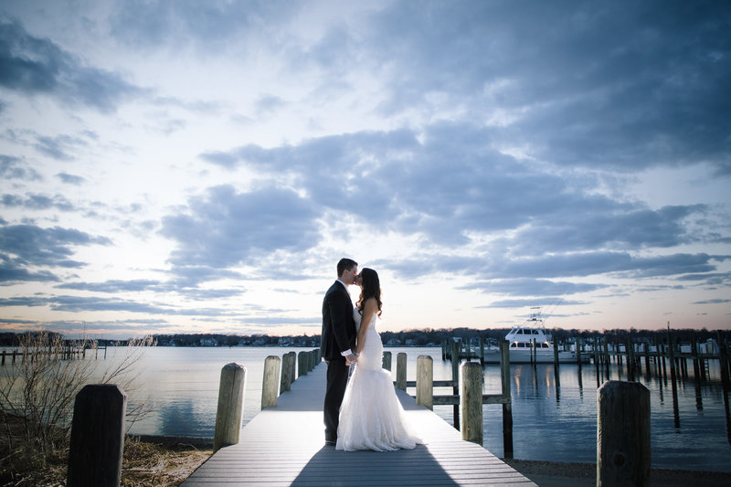 bride and groom kissing at sunset on dock