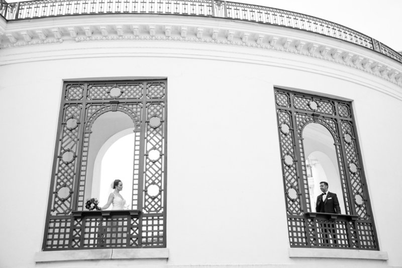 black and white bride and groom stand in windows