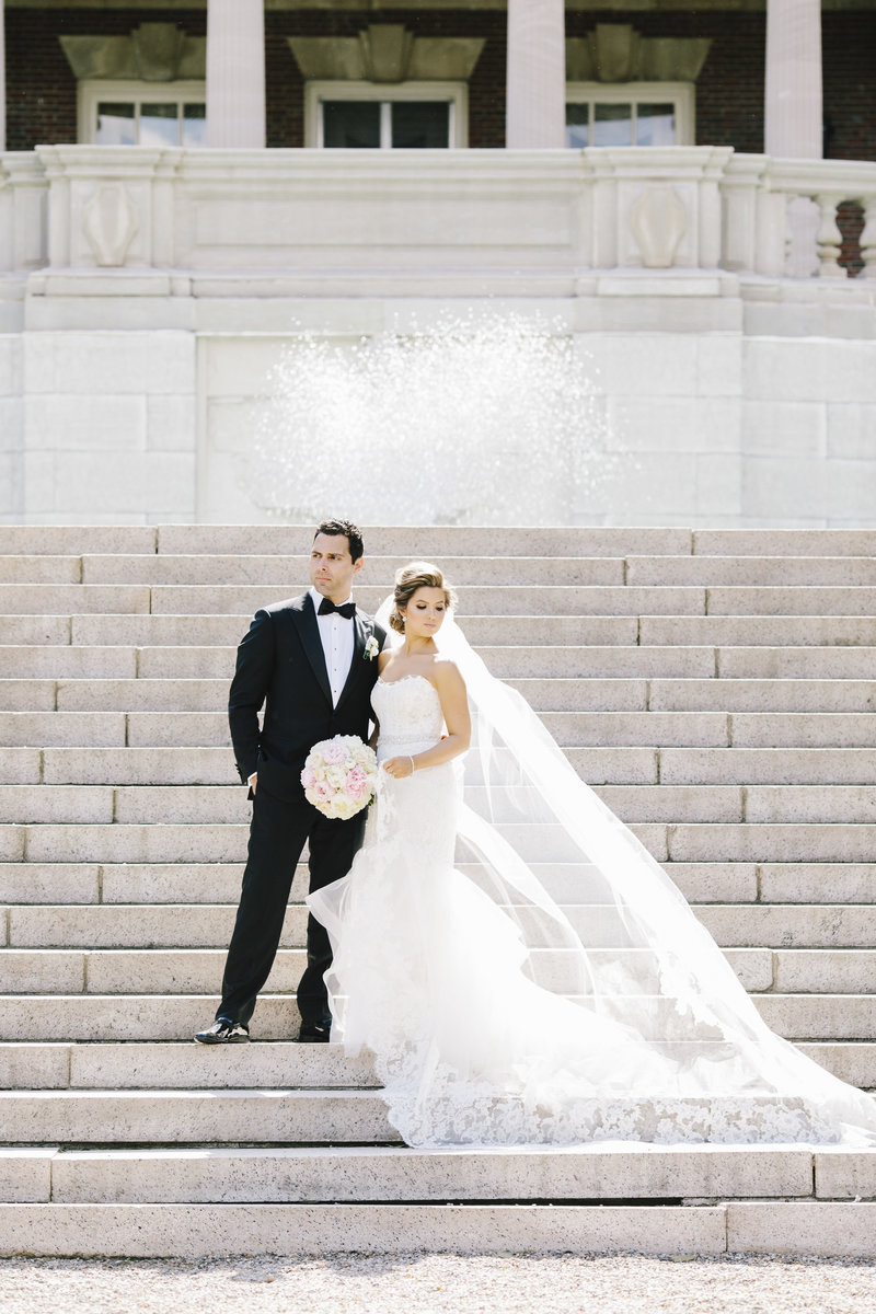 bride and groom stand on grand staircase outside