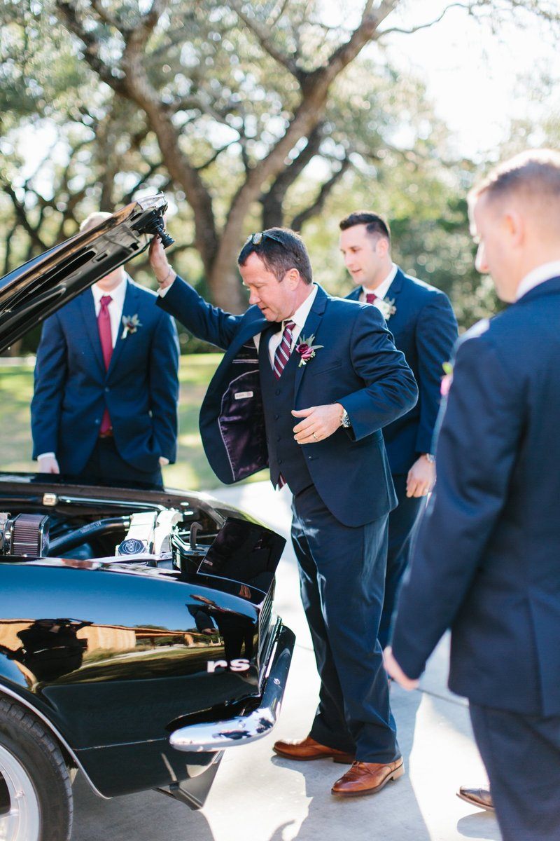 Groomsmen and old camaro getaway car