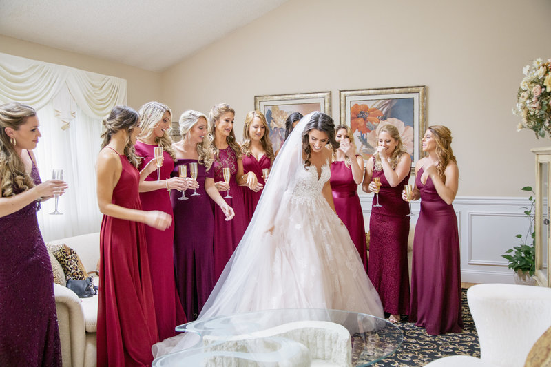 bride shows off her wedding dress to bridesmaids wearing maroon