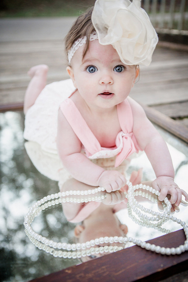 Little girl lays on her stomach on a mirror with a big boy on her head and pearls around her neck at Adair Park by Knoxville Wedding Photographer, Amanda May Photos.