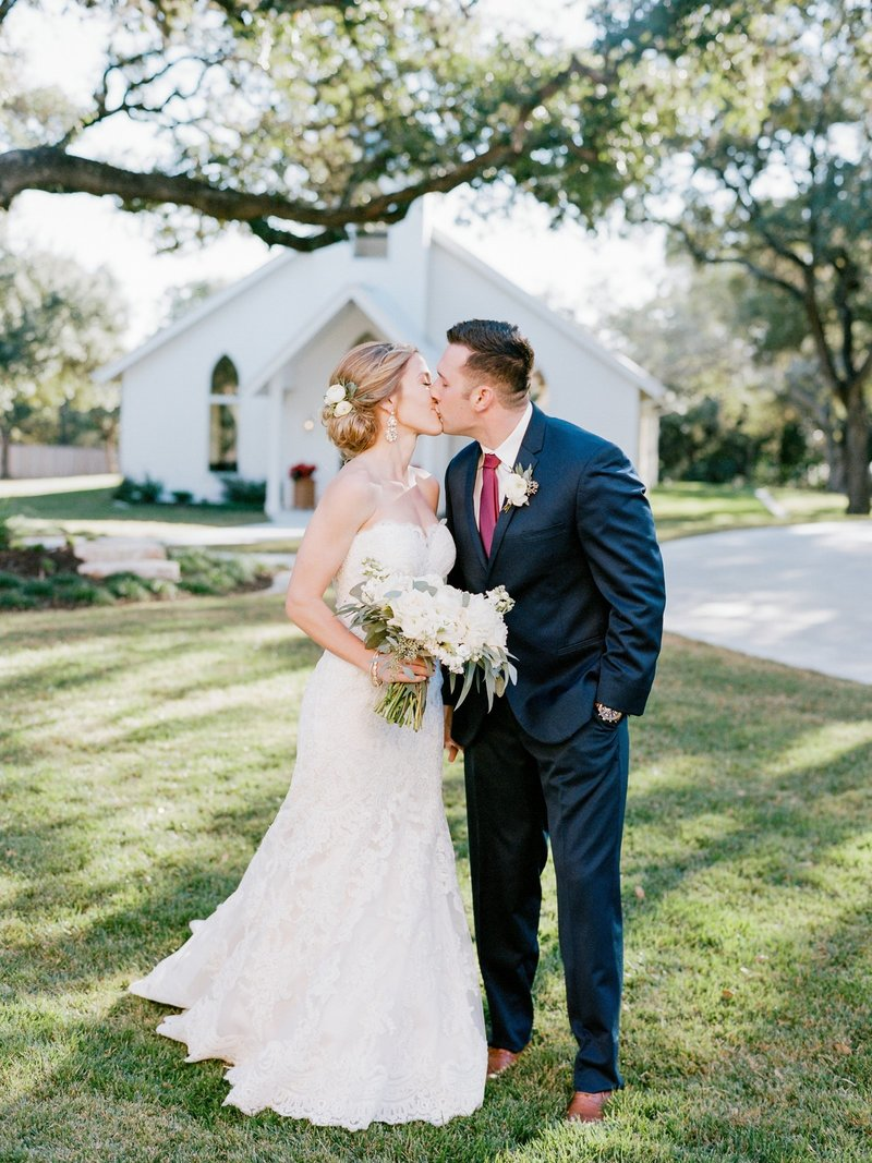 Bride and Groom outside of their white outdoor chapel. captured on film