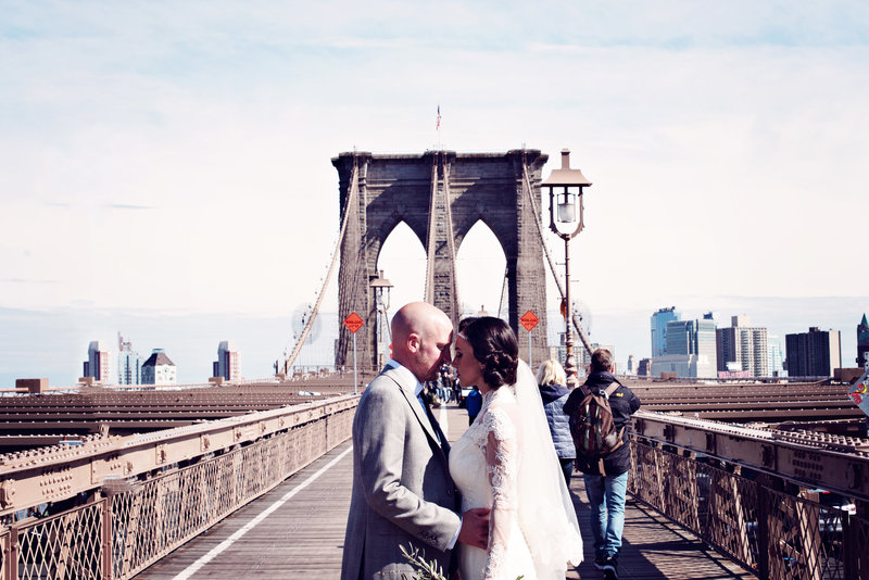 Bride and Groom from Preston stand on the Brooklyn Bridge in New York City after saying i do