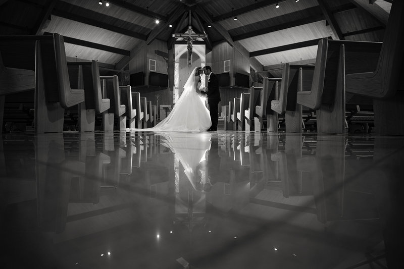 black and white photo of bride and groom kissing at church with reflection on floor