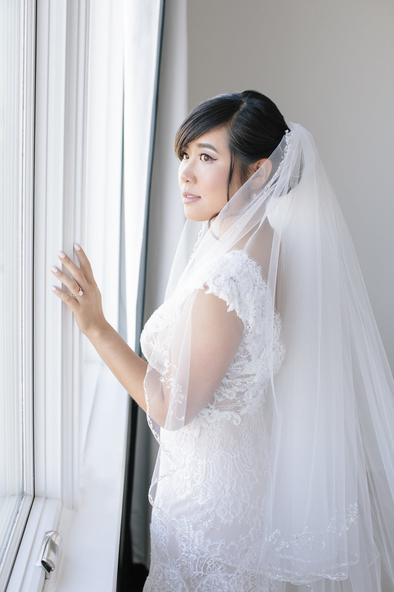 bride looks out white window